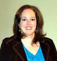 Portrait of Julie Davis, VA, wearing a blue top and black sweater
