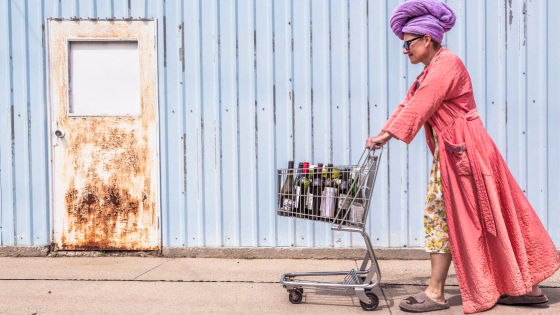 woman in a robe pushing a grocery cart full of bottles